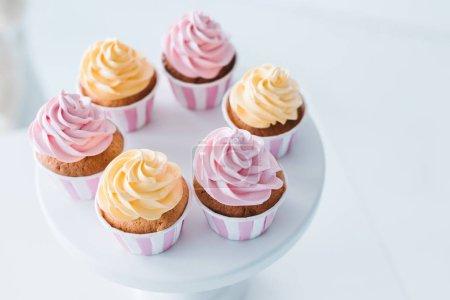 Photo pour Foyer sélectif de délicieux cupcakes sur le stand à la table - image libre de droit