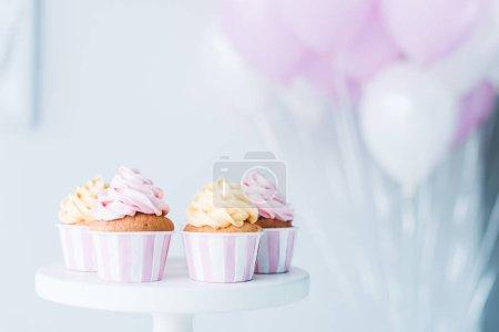 Photo pour Foyer sélectif de stand avec de délicieux cupcakes devant un tas de ballons à air - image libre de droit