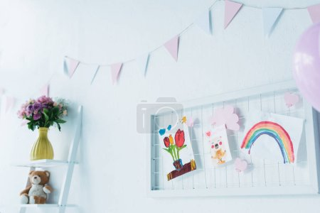 decorated for birthday room with balloons and child paintings