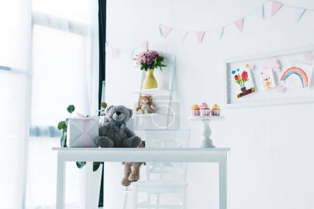 decorated for birthday room with teddy bear, gift box and cupcakes on table