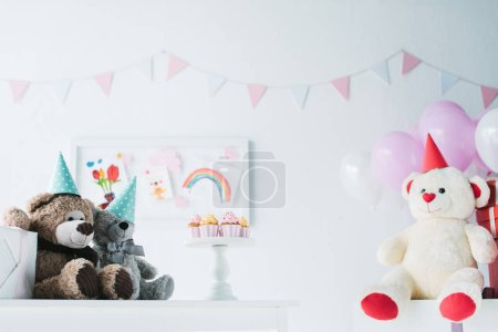 teddy bears in cones on table with cupcakes on stand in decorated for birthday room