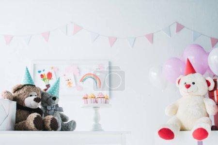 Photo pour Ours en peluche dans les cônes sur table avec des petits gâteaux sur stand décorées pour salle d'anniversaire - image libre de droit