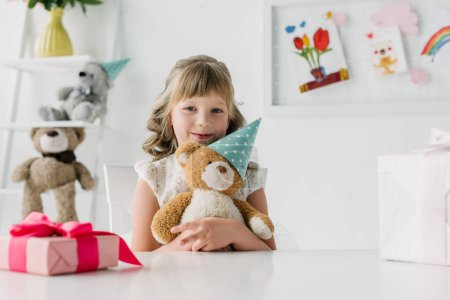 cute birthday child holding teddy bear in cone at table with gift box