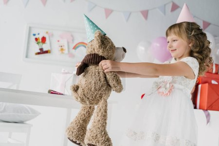 side view of smiling birthday kid holding teddy bear in cone