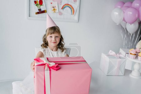 smiling birthday kid in cone sitting at table with huge gift box
