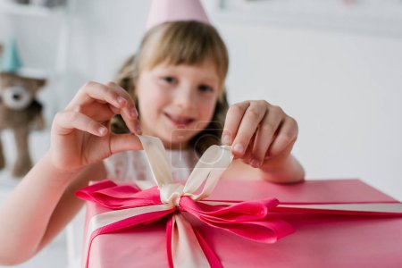selective focus of kid in cone opening birthday gift