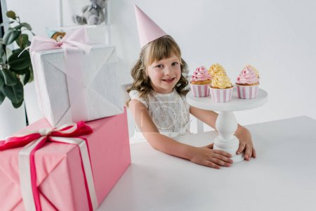 smiling birthday kid in cone sitting at table with cupcakes and gift boxes