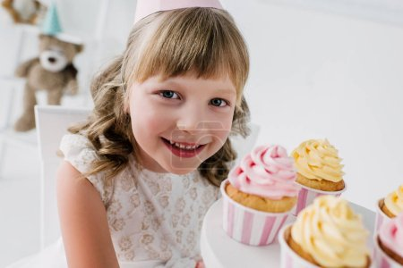 close up portrait of smiling birthday kid in cone looking at camera and showing cupcakes