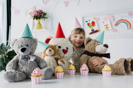 smiling birthday child sitting with teddy bears in cones at table with cupcakes