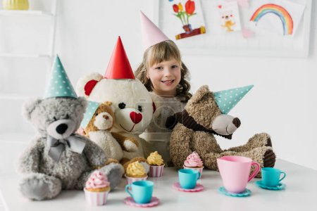 smiling birthday kid with teddy bears in cones having tea party with cupcakes at table