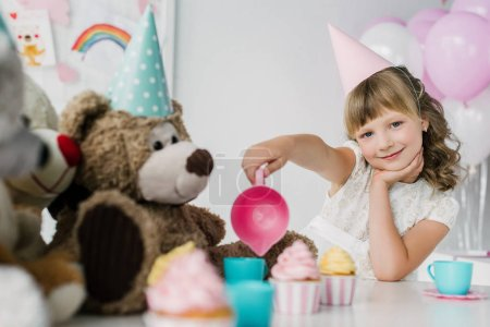 smiling birthday child having tea party with teddy bears in cones