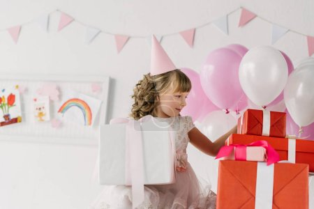 cute birthday child in cone looking at gift boxes