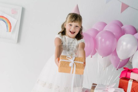 happy birthday child in cone looking at camera and showing gift box