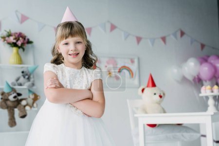 smiling birthday girl in cone standing with crossed arms and looking at camera