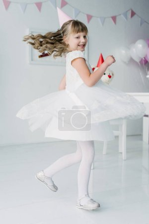 happy little birthday girl in white dress dancing