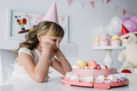 upset lonely child in cone sitting at table with birthday cake
