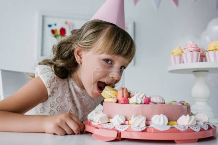 smiling little child in cone eating birthday cake and looking at camera