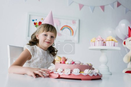 happy adorable child in cone sitting at table with birthday cake