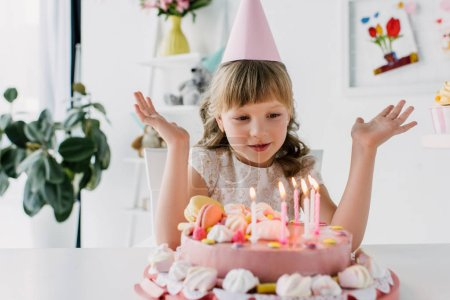 cute kid with wide arms looking at birthday cake with candles