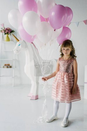 smiling birthday child holding bunch of air balloons and standing with decorative unicorn