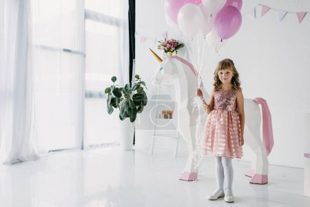 birthday kid holding bunch of air balloons and standing with decorative unicorn