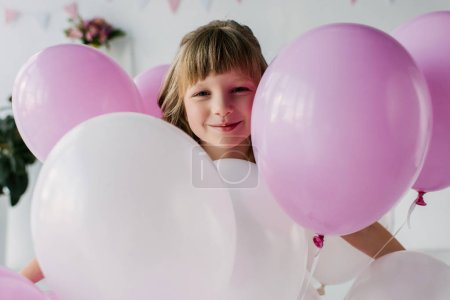 portrait of smiling adorable child standing with air balloons
