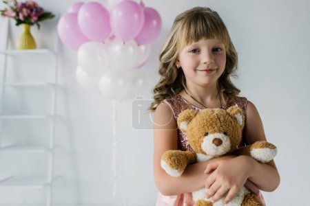 happy child looking at camera and embracing teddy bear