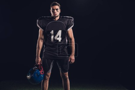 handsome american football player in black uniform holding helmet and looking at camera isolated on black
