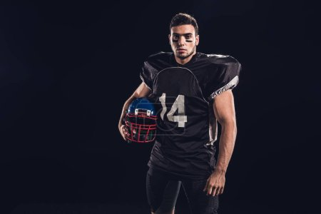 athletic american football player in black uniform holding helmet and looking at camera isolated on black