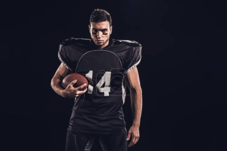 Photo for Young confident american football player with ball looking at camera isolated on black - Royalty Free Image
