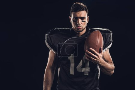 young serious american football player with ball looking at camera isolated on black