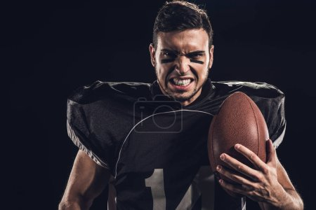 close-up portrait of angry american football player with ball looking at camera isolated on black