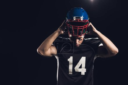 young american football player putting on helmet isolated on black