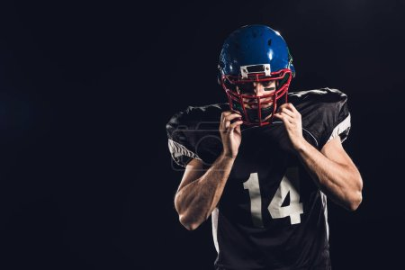 american football player putting on helmet and looking at camera isolated on black