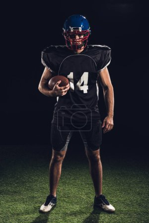 confident american football player holding ball in hand and looking at camera isolated on black