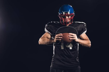 confident american football player holding ball in hands and looking at camera isolated on black