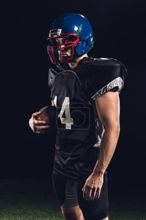confident handsome american football player with ball looking away on black