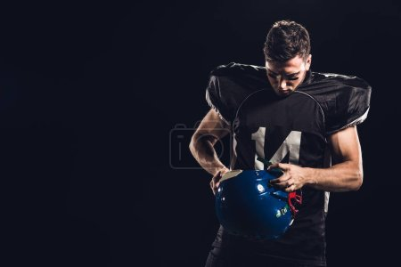 american football player in black uniform with helmet in hands isolated on black