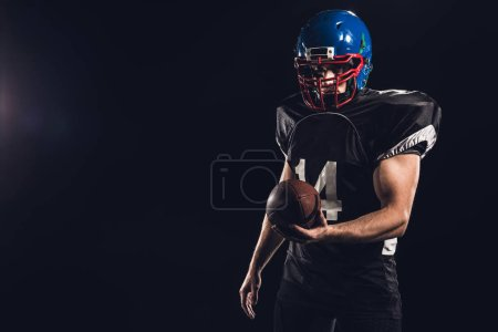 handsome american football player with ball looking at camera isolated on black
