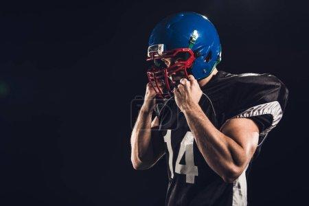 american football player putting on helmet isolated on black