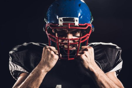 close-up portrait of angry american football player in helmet looking at camera isolated on black