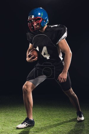 american football player with ball on green grass on black