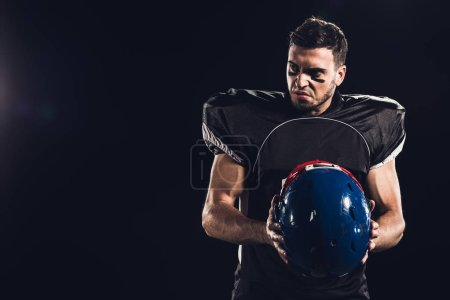 angry american football player in black uniform holding helmet and looking away isolated on black