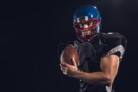 Photo pour Joueur de football américain avec ballon regardant caméra isolée sur noir - image libre de droit
