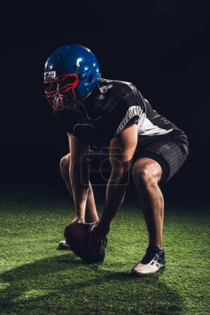 american football player standing squats on grass with ball between feet on black