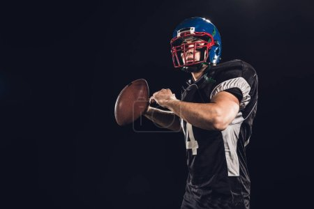 american football player throwing ball isolated on black
