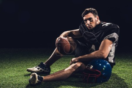 american football player sitting on grass with ball and helmet on black