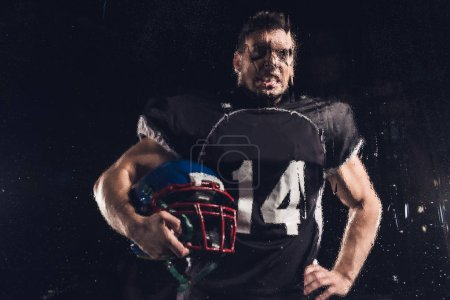 view of angry american football player with helmet on black through wet glass