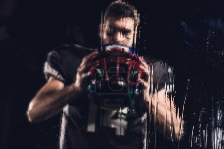 view of american football player holding helmet on black through wet glass