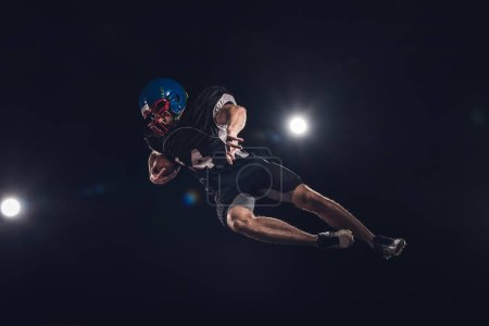 bottom view of american football player jumping with ball under spotlights on black